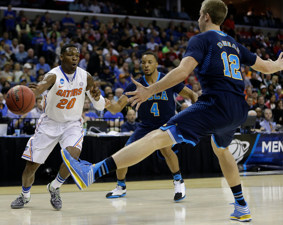 . Florida guard Michael Frazier II (20) passes the ball against UCLA forward David Wear (12) during the first half in a regional semifinal game at the NCAA college basketball tournament, Thursday, March 27, 2014, in Memphis, Tenn. (AP Photo/Mark Humphrey)