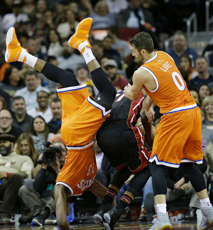 . Cleveland Cavaliers\' Tristan Thompson, left, goes over Miami Heat\'s Hassan Whiteside\'s back as Kevin Love (0) watches in the first half of an NBA basketball game Friday, Dec. 9, 2016, in Cleveland. (AP Photo/Tony Dejak)