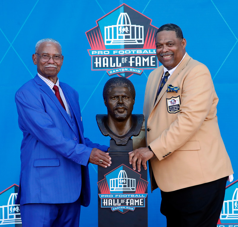 . Former NFL player Robert Brazile, right, poses with a bust of himself and with his father and presenter, Robert Brazile Sr., during the induction ceremony at the Pro Football Hall of Fame, Saturday, Aug. 4, 2018, in Canton, Ohio. (AP Photo/Gene J. Puskar)
