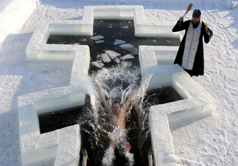 Description of . A Belarus Orthodox believer plunges into icy waters as a priest blesses him on the eve of the Epiphany holiday in Pilnitsa some 30 km outside Minsk, on January 18, 2013. Thousands of believers jumpe into holes cut in ice, braving freezing temperatures, on January 18 and early on January 19 to mark Epiphany, when they take part in a baptism ceremony. VIKTOR DRACHEV/AFP/Getty Images