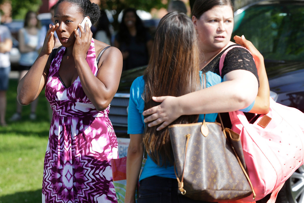 . Brianna Clarke, left, cries as she talks on her phone while Erin Rutledge, right, an athletic trainer at Seattle Pacific University, is hugged by a colleague, at the scene of a shooting Thursday, June 5, 2014 at Seattle Pacific University in Seattle. About 4,270 students attend the private Christian university, located in a residential neighborhood about 10 minutes from downtown Seattle. (AP Photo/Ted S. Warren)