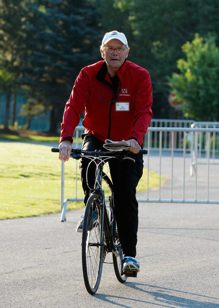 . Journalist Tom Brokaw arrives by bicycle for the Allen & Co. annual conference at the Sun Valley Resort on July 10, 2013 in Sun Valley, Idaho. The resort is hosting corporate leaders for the 31st annual Allen & Co. media and technology conference where some of the wealthiest and most powerful executives in media, finance, politics and tech gather for weeklong meetings. Past attendees included Warren Buffett, Bill Gates and Mark Zuckerberg.  (Photo by Kevork Djansezian/Getty Images)