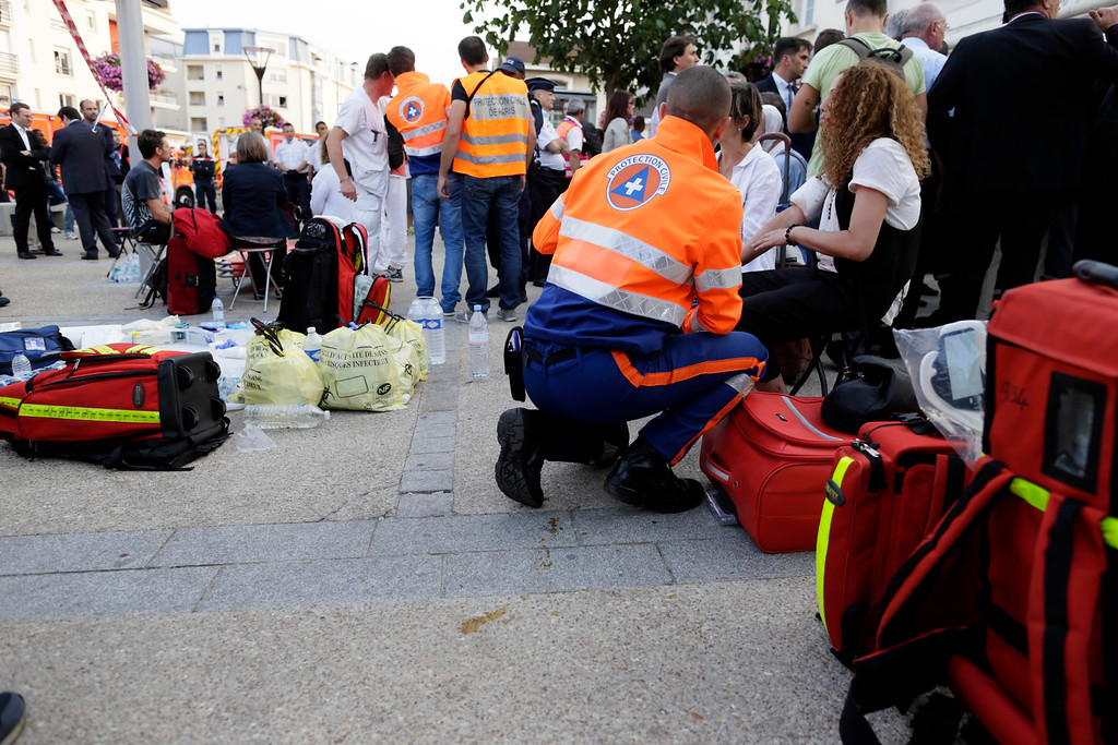 . Rescue workers tend to victims at the site of a train accident in the railway station of Bretigny-sur-Orge, Friday, July 12, 2013 near Paris. (AP Photo/Kenzo Tribouillard, Pool)