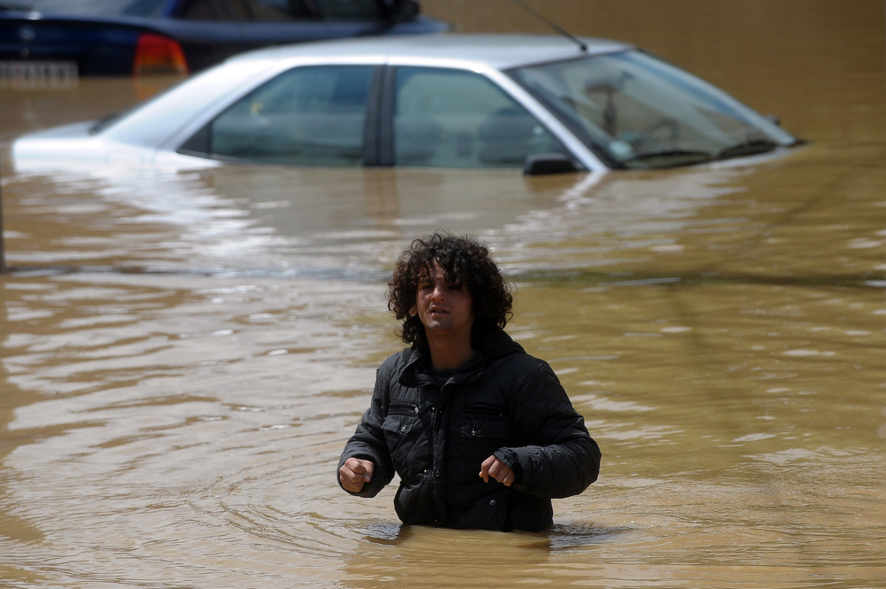 Description of . A man walks trough a flooded street in the town of Obrenovac, 40 kilometers west of Belgrade, on May 17, 2014. Deadly floods across Bosnia and Serbia have claimed at least 14 lives and led to the evacuation of 15,000 people after the Balkans suffered its heaviest rainfall in a century, officials said on Saturday. (ALEXA STANKOVIC/AFP/Getty Images)