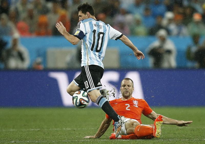 . Argentina\'s forward and captain Lionel Messi controls the ball Netherlands\' defender Ron Vlaar falls during the semi-final football match between Netherlands and Argentina of the FIFA World Cup at The Corinthians Arena in Sao Paulo on July 9, 2014. (ADRIAN DENNIS/AFP/Getty Images)