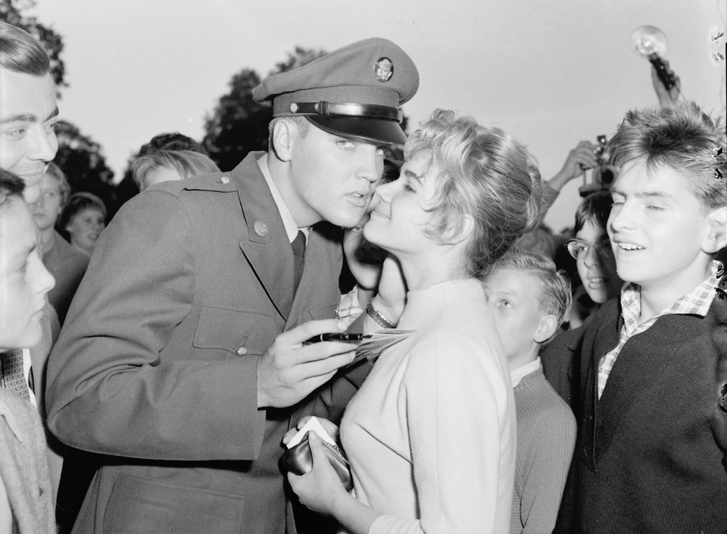 . Seventeen year old Margit Burgin of Frankfurt is kissed by Pvt. Elvis Presley at the request of photographers in Bad Homburg, West Germany October 8, 1958.  Presley, assigned to the Third Armored Division at Friedberg, was at liberty on a weekend pass and spent most of the time with his father and grandmother in Bad Homburg. (AP Photo)