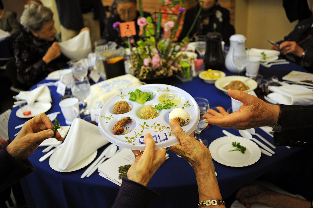 . A Seder plate is passed around a table during a traditional Passover Seder for both residents of the Los Angeles Jewish Home and visiting residents of Keiro Senior Healthcare Wednesday in Reseda, CA.(Andy Holzman/Los Angeles Daily News)