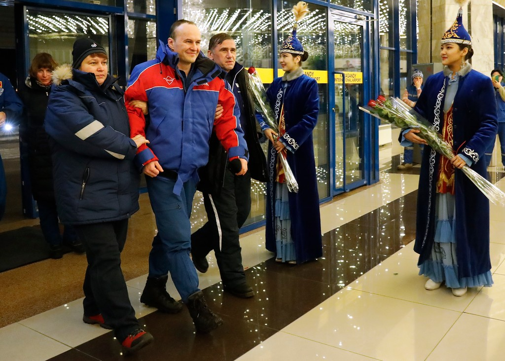 . Russian cosmonaut Sergey Ryazanskiy, center, is assisted by Russian space agency specialists walks at the airport of Karaganda, Kazakhstan, Thursday, Dec. 14, 2017. Three astronauts on Thursday landed back on Earth after nearly six months aboard the International Space Station. (AP Photo/Dmitri Lovetsky, Pool)