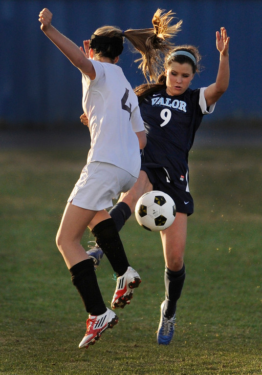 . PARKER, CO. - APRIL 2: Golden defender Riley Sanders (4) challenged Valor forward Hannah Hommel (9) in the second half. The Valor Christian High School girl\'s soccer team defeated Golden 4-1 Wednesday night, April 3, 2013.  Photo By Karl Gehring/The Denver Post)