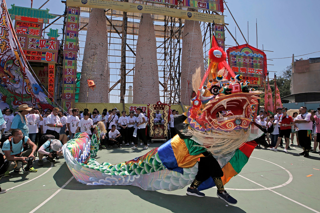. Villagers perform lion dance during a parade in front of the bun towers on the outlying Cheung Chau island in Hong Kong to celebrate the Bun Festival Tuesday, May 22, 2018. Thousands of local residents and tourists flocked to an outlying island in Hong Kong to celebrate a local bun festival on Tuesday despite the recording-breaking heat.  The festival features a parade with children dressed as deities floated on poles. Later on Tuesday, contestants will take part in bun-scrambling competition. They will race up a 14-meter bamboo tower to snatch as many plastics buns as possible. Buns that are higher up are worth more points.  (AP Photo/Kin Cheung)