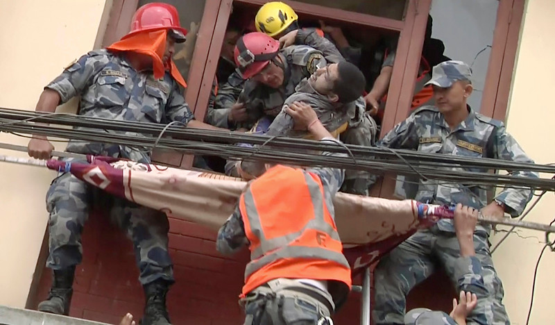 . In this image made from video, rescue workers pull a survivor from an earthquake damaged building in Kathmandu, Nepal, Sunday, April 26, 2015. A strong magnitude 7.8 earthquake shook Nepal\'s capital and the densely populated Kathmandu Valley before noon Saturday, causing extensive damage with toppled walls and collapsed buildings. (APTN via AP)