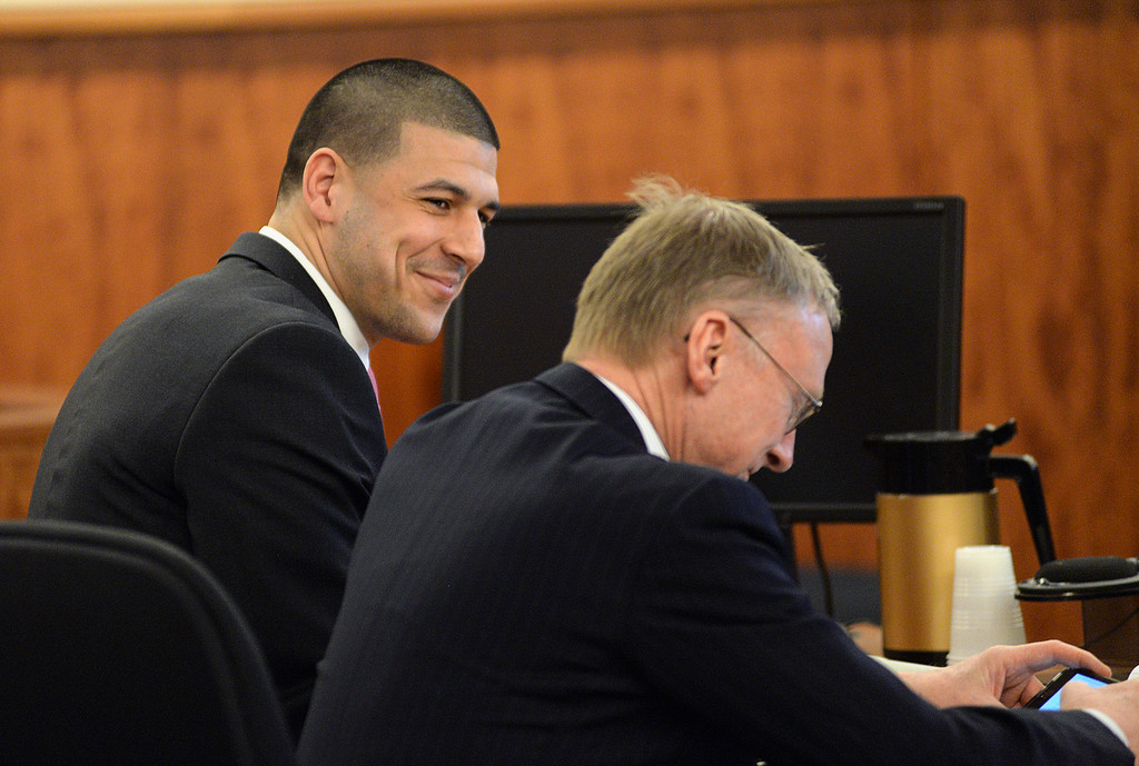 . Former New England Patriots football player Aaron Hernandez smiles with defense attorney Charles Rankin in the courtroom of the Bristol County Superior Court House in Fall River, Mass., Wednesday, April 8, 2015. The fate of Hernandez is now in the hands of a jury, which began its first full day of deliberations Wednesday in his murder trial. Hernandez is charged with the June 2013 shooting death of Odin Lloyd. (AP Photo/Faith Ninivaggi, Pool)