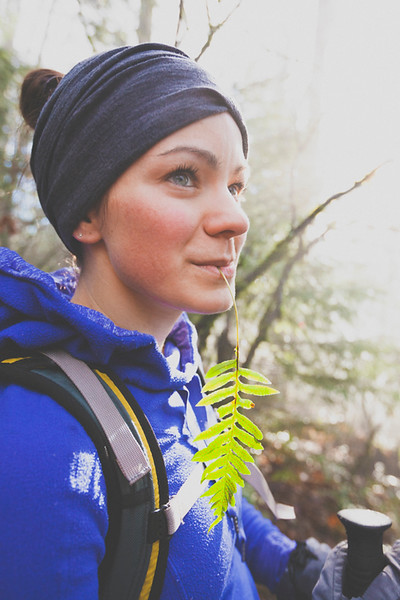 A young woman  chews on a Licorice Fern while hiking.
