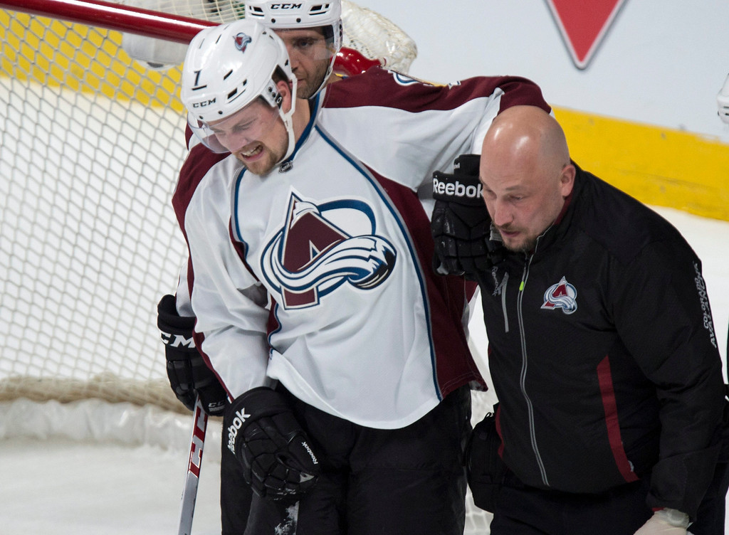 . Colorado Avalanche\'s John Mitchell is helped off the ice after being injured as they face the Montreal Canadiens during second period NHL hockey action Tuesday, March 18, 2014 in Montreal.  (AP Photo/The Canadian Press, Paul Chiasson)