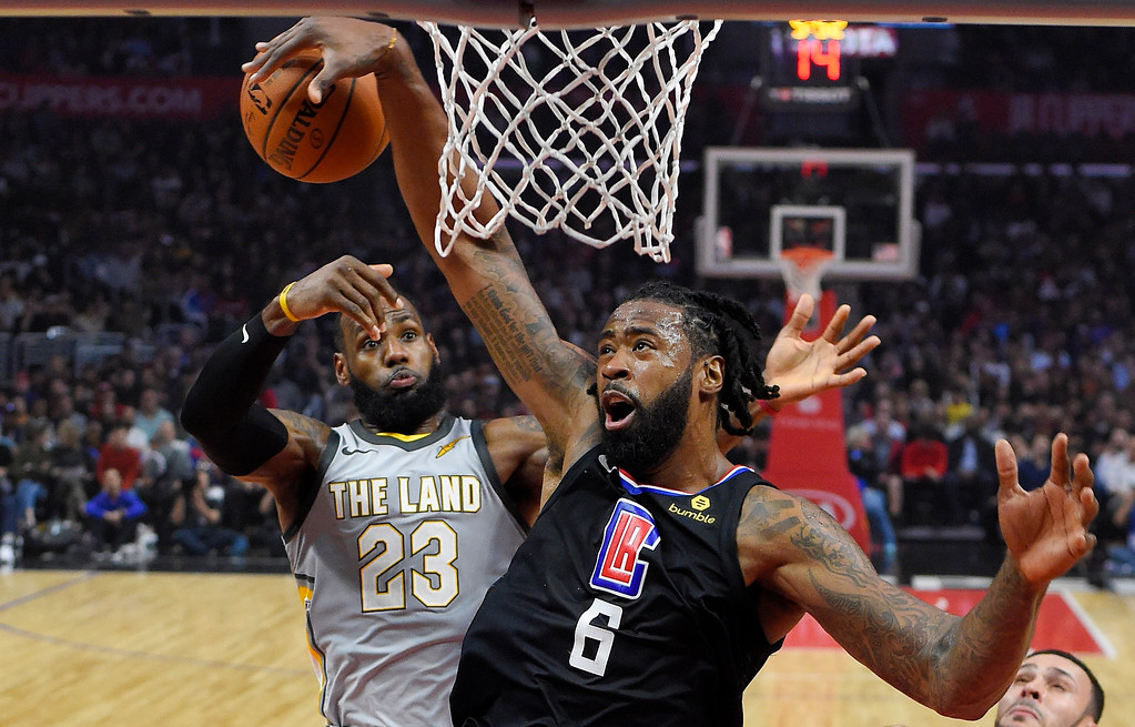 . Los Angeles Clippers center DeAndre Jordan tries to get control of the ball after his shot was blocked by Cleveland Cavaliers forward LeBron James, rear, during the first half of an NBA basketball game, Friday, March 9, 2018, in Los Angeles. (AP Photo/Mark J. Terrill)