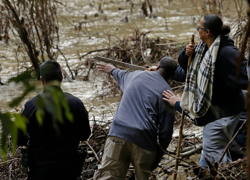 . The parents of a missing 18-year-old woman look at what they believe to be their daughter\'s submerged car in Alameda Creek on Monday, Jan. 23, 2017, near Fremont, Calif. The unidentified woman\'s car plunged into rushing waters after colliding with another vehicle on Saturday, Jan. 21, 2017, and she is suspected of being in the submerged vehicle. (AP Photo/Ben Margot)