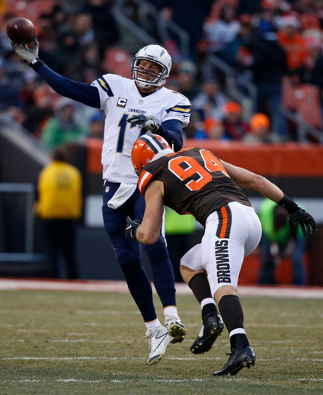 . San Diego Chargers quarterback Philip Rivers (17) throws under pressure from Cleveland Browns defensive end Carl Nassib (94) in the second half of an NFL football game, Saturday, Dec. 24, 2016, in Cleveland. (AP Photo/Ron Schwane)