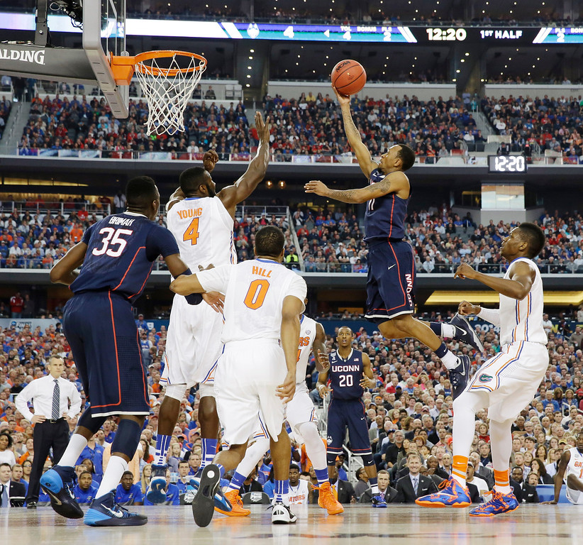 . Connecticut guard Ryan Boatright shoots as Florida center Patric Young (4) defends during the first half of the NCAA Final Four tournament college basketball semifinal game Saturday, April 5, 2014, in Arlington, Texas. (AP Photo/David J. Phillip)