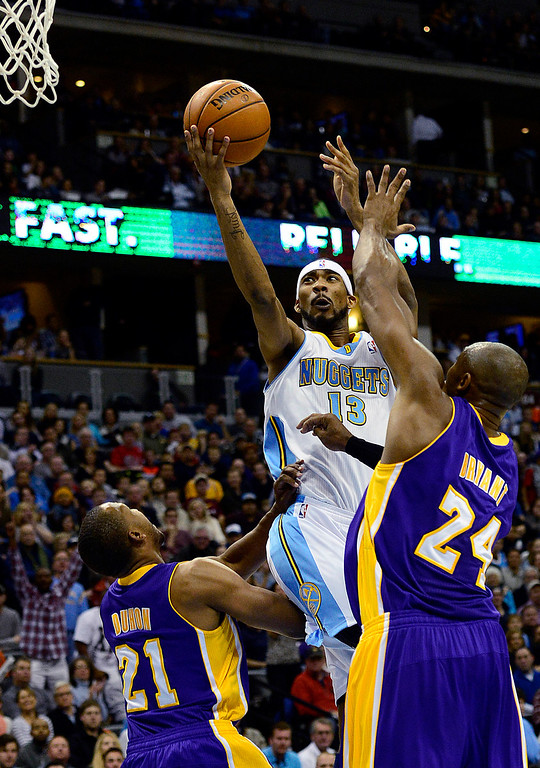 . Denver Nuggets small forward Corey Brewer (13) drives on Los Angeles Lakers shooting guard Kobe Bryant (24) and point guard Chris Duhon (21) during the first half at the Pepsi Center on Wednesday, December 26, 2012. AAron Ontiveroz, The Denver Post