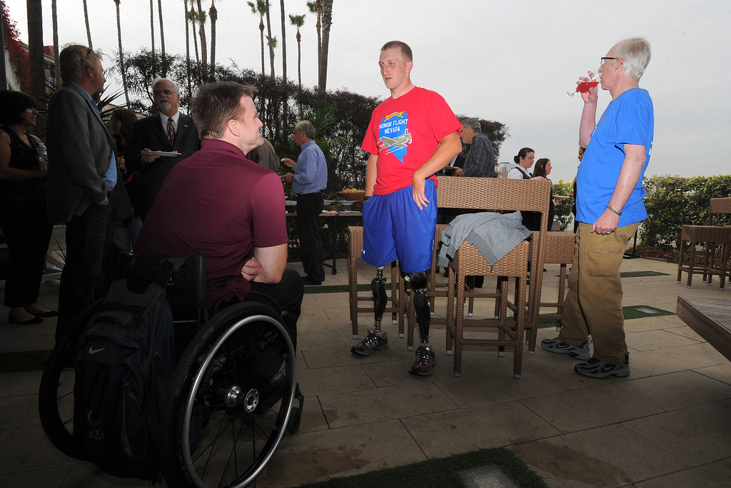 . Double amputee marine veteran Rob Jones, center, chats with his 2012 Paralympics rowing teammate Ron Harvey, left, and Jones\' father, Lenny, at a reception at the Hotel Maya in Long Beach, CA on Thursday, April 10, 2014. Jones began riding his bicycle across the country in Maine in October and will his fundraising journey Saturday at Camp Pendleton. (Photo by Scott Varley, Daily Breeze)