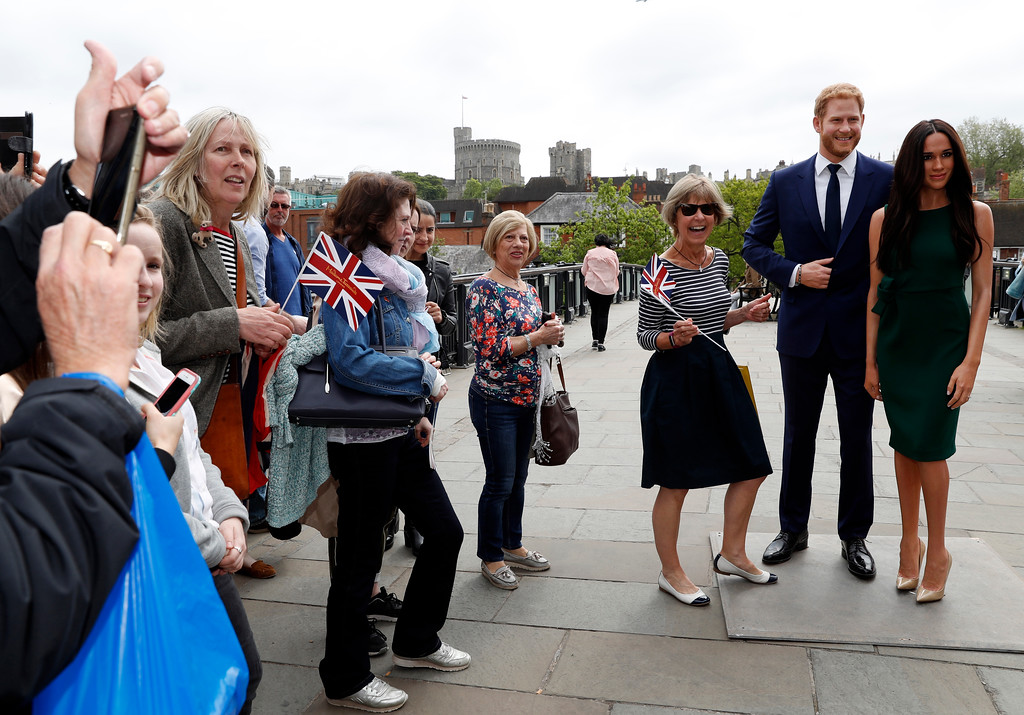 . Tourists gather to take photos with waxwork figures of Britain\'s Prince Harry and Meghan Markle against the backdrop of Windsor Castle, in Windsor, England, Wednesday, May 16, 2018. Preparations continue in Windsor ahead of the royal wedding of Britain\'s Prince Harry and Meghan Markle Saturday May 19. (AP Photo/Alastair Grant)