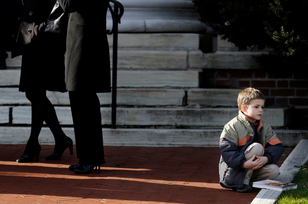 . A boy sits near the steps of a church a church  before the memorial service for Lauren Rousseau in Danbury, Conn., Thursday, Dec. 20, 2012.   Rousseau, 30, was killed when Adam Lanza walked into Sandy Hook Elementary School in Newtown, Dec. 14, and opened fire, killing 26 people, including 20 children, before killing himself.  (AP Photo/Seth Wenig)