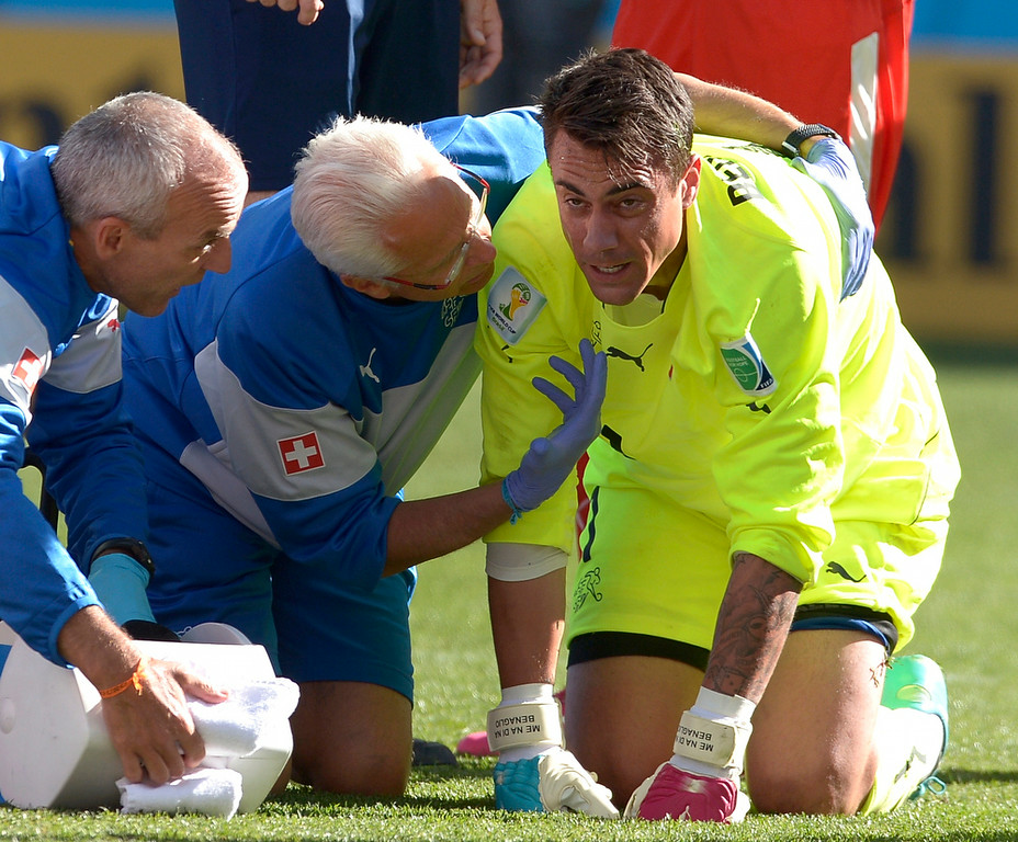 . Trainers examine Switzerland\'s goalkeeper Diego Benaglio after he was run over by Argentina\'s Rodrigo Palacio during the World Cup round of 16 soccer match between Argentina and Switzerland at the Itaquerao Stadium in Sao Paulo, Brazil, Tuesday, July 1, 2014. (AP Photo/Manu Fernandez)