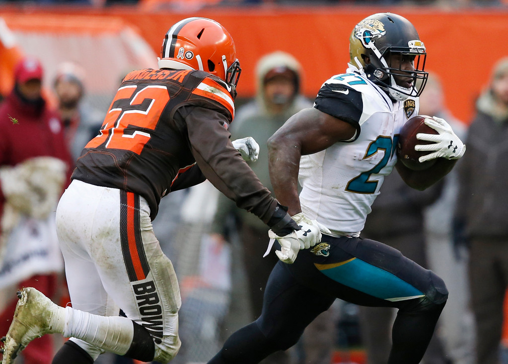 . Jacksonville Jaguars running back Leonard Fournette (27) rushes against Cleveland Browns inside linebacker James Burgess (52) in the second half of an NFL football game, Sunday, Nov. 19, 2017, in Cleveland. (AP Photo/Ron Schwane)