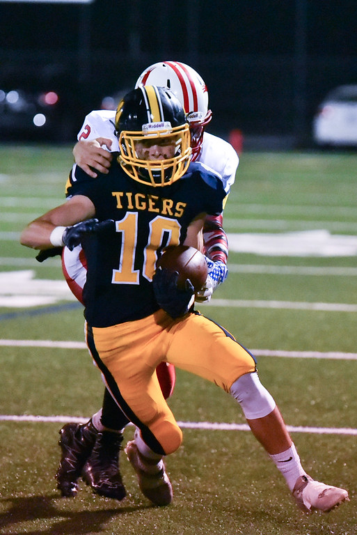 . Littleton senior Mike Crory carries the ball through the 50 yard line as Hudson defense attempts to pull him down during Friday night\'s football game at Littleton Middle School.  Sun/Jeff Porter