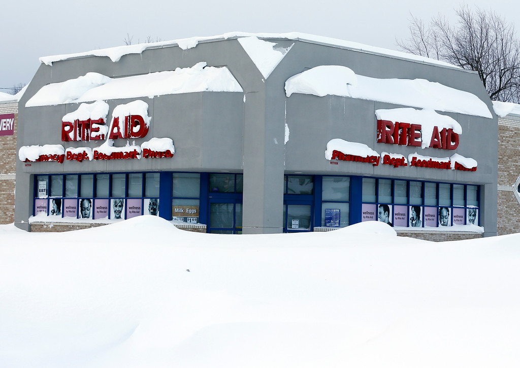 . A Rite Aid store is covered in snow in the south Buffalo area on Thursday, Nov. 20, 2014, in Buffalo, N.Y.  A new blast of lake-effect snow pounded Buffalo for a third day piling more misery on a city already buried by an epic, deadly snowfall that could leave some areas with nearly 8 feet of snow on the ground when it\'s all done. (AP Photo/Mike Groll)