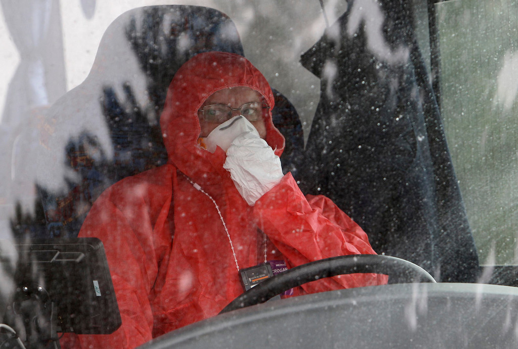. A worker wearing a protective suit adjusts his mask as he drives a bus during a nuclear accident simulation as part of a safety regulations exercise at Nuclear Power Plant Dukovany in Dukovany March 26, 2013.     REUTERS/David W Cerny