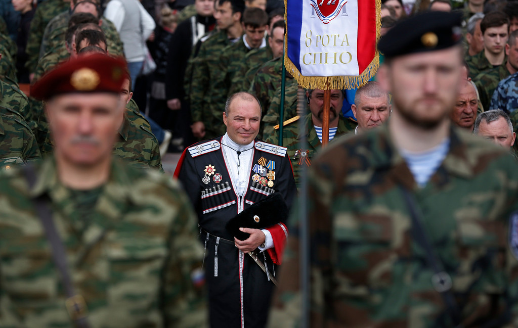 . Members of the Crimean self defense forces attend a celebration of the 70th anniversary of the liberation of Simferopol, Crimea, Sunday, April 13, 2014. On Sunday, residents of Simferopol mark the 70th anniversary of the liberation of Simferopol from German troops during World War II. (AP Photo/Max Vetrov)