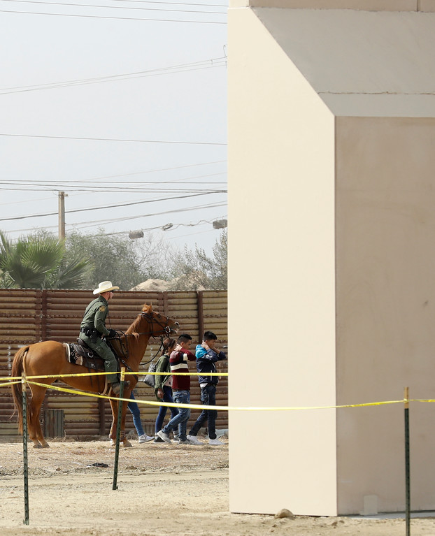 . A group of people are detained by Border Patrol agents on horseback after crossing crossing the border illegally from Tijuana, Mexico, near prototypes for a border wall, right, are being constructed Thursday, Oct. 19, 2017, in San Diego. Companies are nearing an Oct. 26 deadline to finish building eight prototypes of President Donald Trump\'s proposed border wall with Mexico. (AP Photo/Gregory Bull)