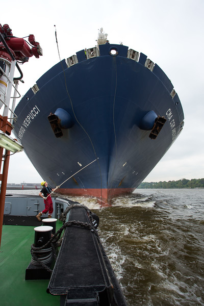 Containerschiff und Schlepper beim anbinden auf der Elbe in Hamburg