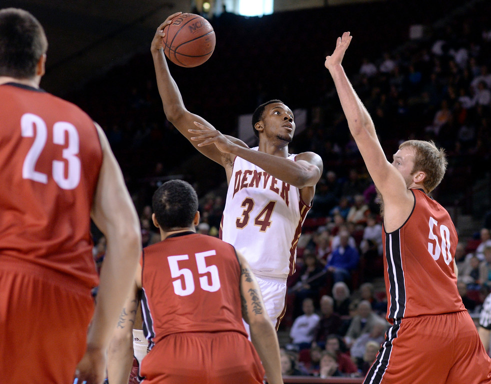 . DENVER, CO. - FEBRUARY 8, 2014: Denver forward Chris Udofia (34) attempted to hook a shot over South Dakota Center Trevor Gruis (50) in the first half. The University of Denver hosted South Dakota Saturday afternoon, February 8, 2014. Photo By Karl Gehring/The Denver Post