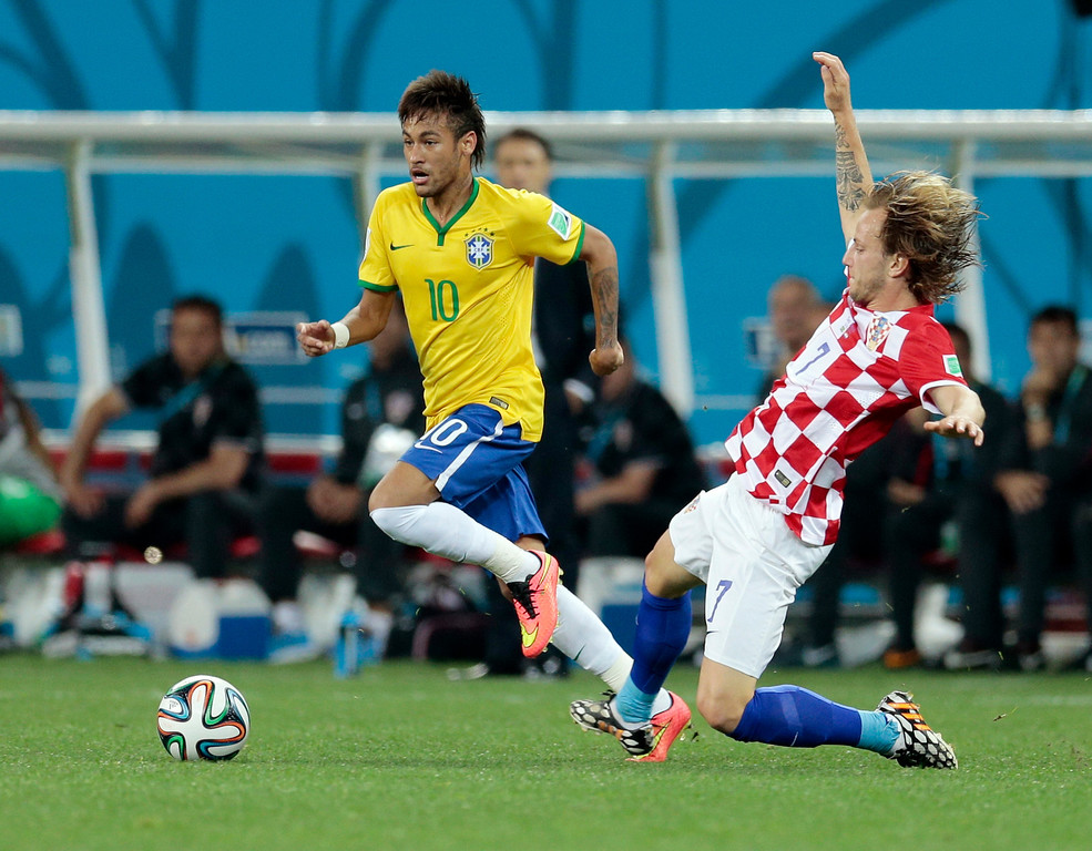 . Croatia\'s Ivan Rakitic tries to stop Brazil\'s Neymar during the group A World Cup soccer match between Brazil and Croatia, the opening game of the tournament, in the Itaquerao Stadium in Sao Paulo, Brazil, Thursday, June 12, 2014.  (AP Photo/Ivan Sekretarev)