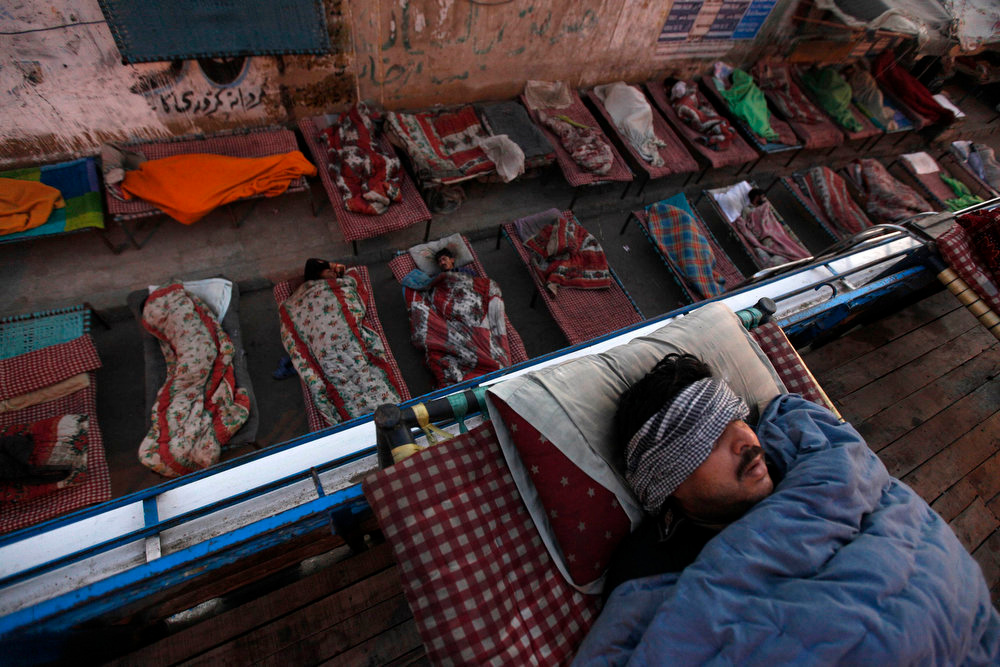 . People sleep on charpoy beds along a road, near a railway station in Karachi April 1, 2013. Charpoy bed guesthouses are only setup at night from 9pm to 7am for the homeless, passengers and drivers, charging about 40 Pakistani rupees ($0.40) per night. REUTERS/Akhtar Soomro