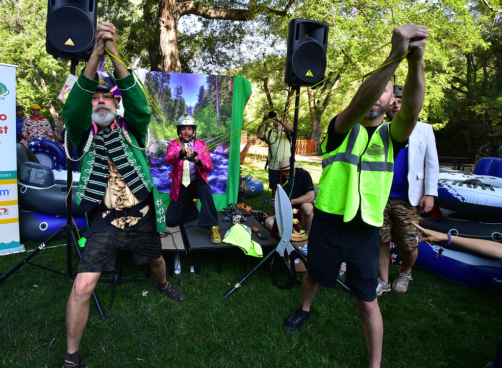 """. Steve \""""Gunter Berlin\"""" Mertz, left, and Raj Seymour, at right, help Jeff Kagan, Tube to Work Day co-founder, fire ties into the crowd at Eben G. Fine Park for the 11th Annual Tube to Work Day on Boulder Creek on Wednesday morning.  Paul Aiken Staff Photographer July 11 2018"""