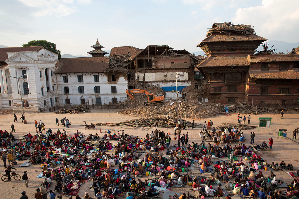 . In this April 26, 2015 file photo, people gather on an open space for security reasons at the Basantapur Durbar Square, damaged in Saturday\'s earthquake in Kathmandu, Nepal. In mere seconds a powerful earthquake flattened a swathe of Nepal. Three of the seven World Heritage sites in the Kathmandu Valley have been severely damaged, including Durbar Square with pagodas and temples dating from the 15th to 18th centuries, according to UNESCO, the United Nations cultural agency.(AP Photo/Bernat Armangue, file)
