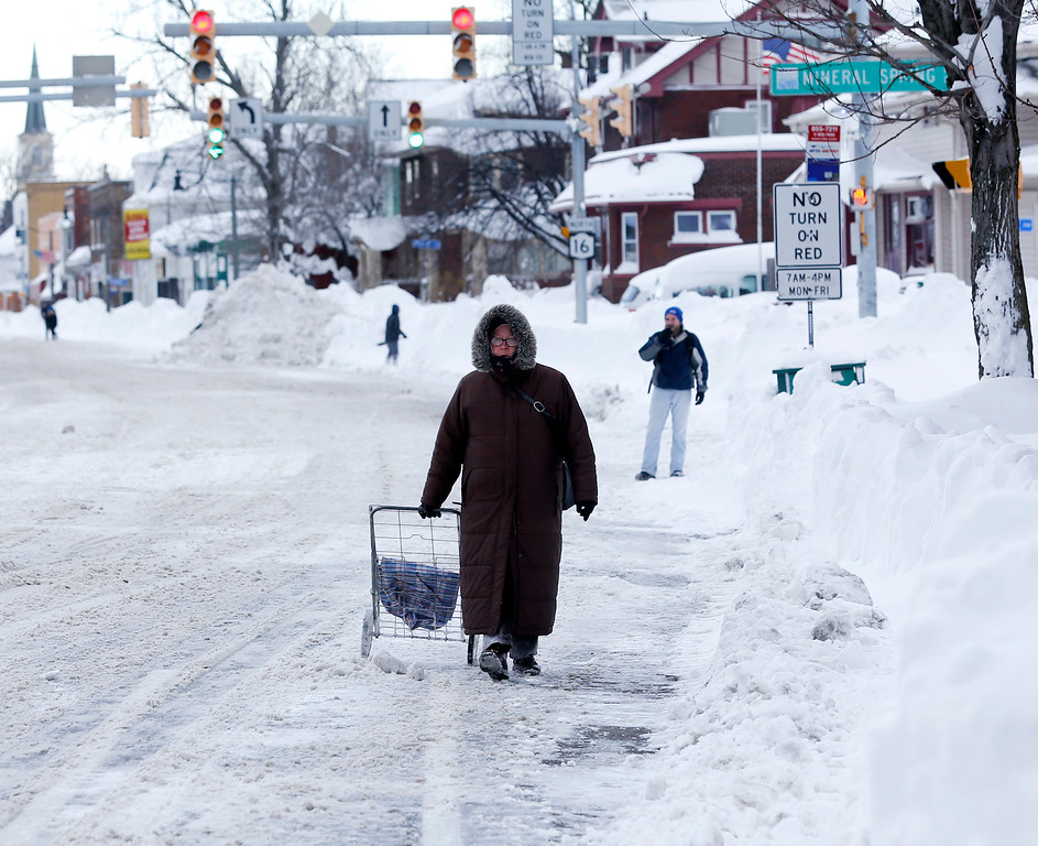 . A woman walks along a snow-covered street in the south Buffalo area on Thursday, Nov. 20, 2014, in Buffalo, N.Y. A new blast of lake-effect snow pounded Buffalo for a third day piling more misery on a city already buried by an epic, deadly snowfall that could leave some areas with nearly 8 feet of snow on the ground when it\'s all done. (AP Photo/Mike Groll)