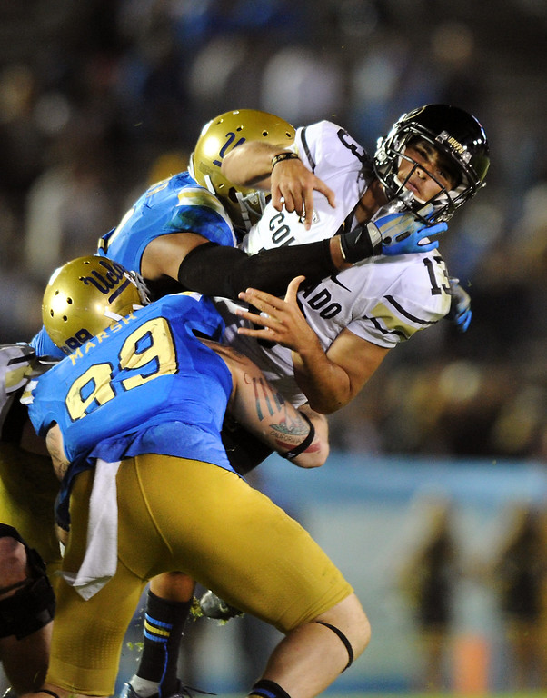 . UCLA\'s Cassius Marsh (#99) and Anthony Barr put the squeeze on Colorado QB Sefo Liufau, Saturday, November 2, 2013, at the Rose Bowl. (Photo by Michael Owen Baker/L.A. Daily News)