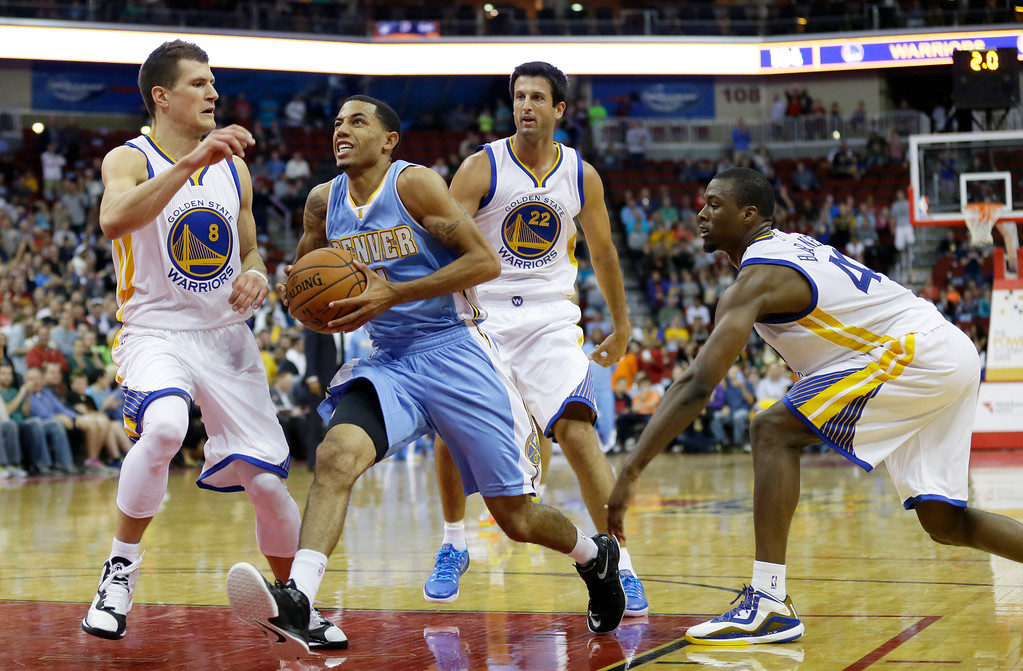 . Denver Nuggets guard Erick Green, center, drives to the basket between Golden State Warriors\' Nemanja Nedovic, left, Jason Kapono, rear, and Harrison Barnes during the second half of a preseason NBA basketball game, Thursday, Oct. 16, 2014, in Des Moines, Iowa. Golden State won 104-101. (AP Photo/Charlie Neibergall)