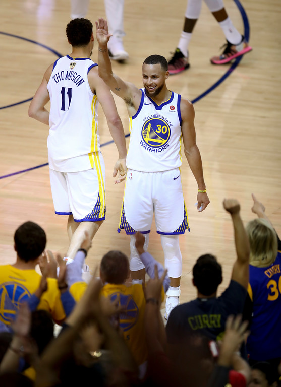 . Golden State Warriors guard Stephen Curry (30) celebrates with guard Klay Thompson (11) in front of fans after scoring against the Cleveland Cavaliers during the first half of Game 1 of basketball\'s NBA Finals in Oakland, Calif., Thursday, May 31, 2018. (AP Photo/Ben Margot)