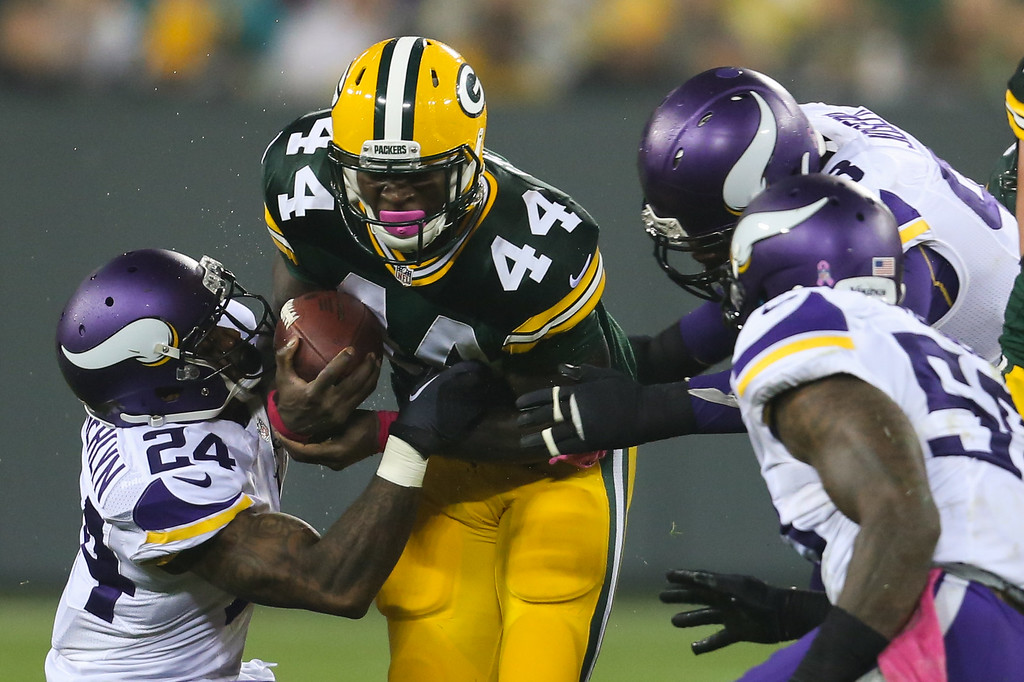 . GREEN BAY, WI - OCTOBER 2:  James Starks #44 of the Green Bay Packers is tackled by Captain Munnerlyn #24 and Linval Joseph #98 of the Minnesota Vikings in the first half of the NFL game on October 02, 2014 at Lambeau Field in Green Bay, Wisconsin. (Photo by John Konstantaras/Getty Images)