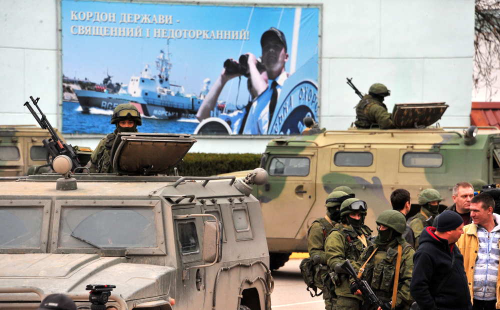 ". Unidentified men in  military fatigues stand in front of a poster reading "" The border of the country - is sacred and untouchable\""  as they block  a base of the Ukrainian frontier guard unit in Balaklava on March 1, 2014.  Ukraine\'s border guard service said  that about 300 armed men were attempting to seize its main headquarters in the Crimean port city of Sevastopol under orders from Russian Defence Minister Sergei Shoigu.  (VIKTOR DRACHEV/AFP/Getty Images)"