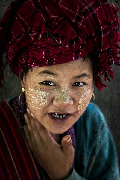 Portrait of a young woman wearing the traditional Thanaka on her face.   Myanmar, 2017