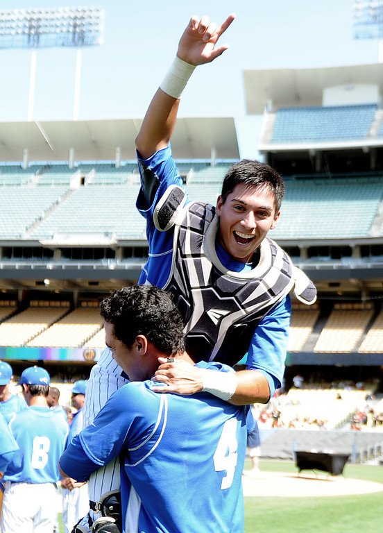 . Bishop Amat\'s Michael Palos jumps into the arms of teammate Alex Garcia (4) as they defeated Palm Desert 4-3 to win the CIF-SS Division 3 baseball championship at Dodger Stadium in Los Angeles on Friday, June 6, 2014. 