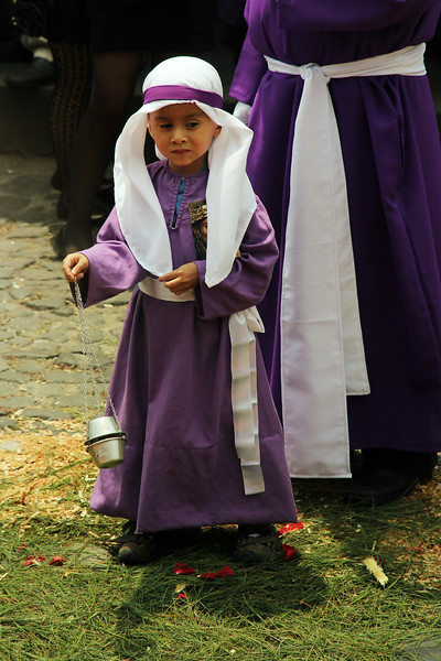 A young boy swings an incense bowl as he walks over an alfombra (carpet) in Antigua, Guatemala during a Lent procession on March 24, 2013.