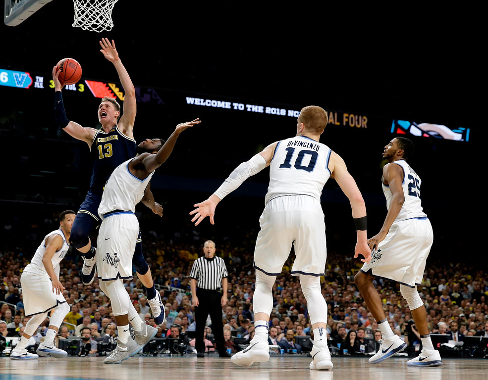 . Michigan forward Moritz Wagner (13) drives to the basket over Villanova forward Eric Paschall during the second half in the championship game of the Final Four NCAA college basketball tournament, Monday, April 2, 2018, in San Antonio. (AP Photo/Eric Gay)