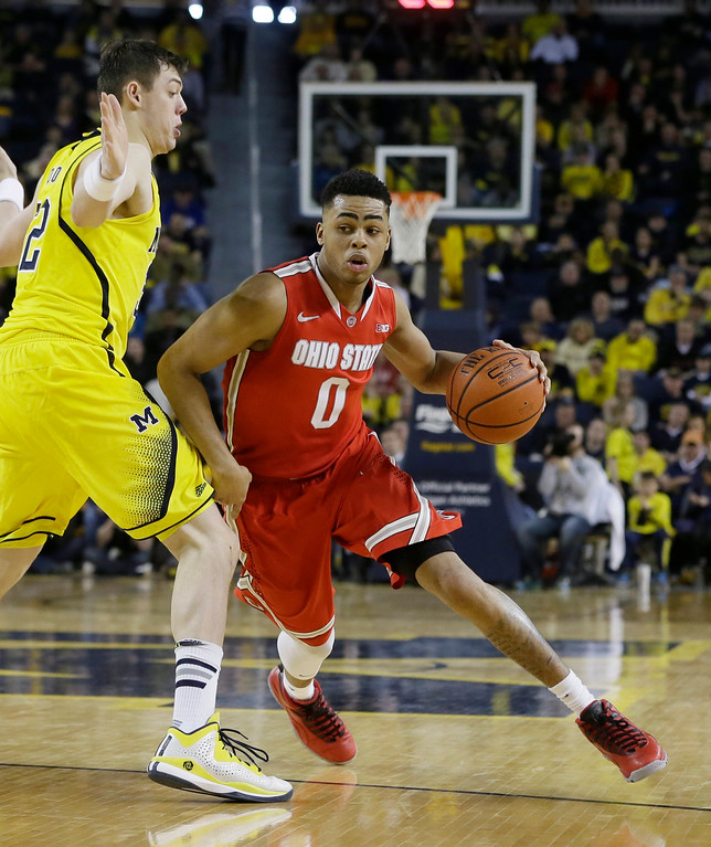 . Ohio State guard D\'Angelo Russell (0) drives on Michigan forward Ricky Doyle during the second half of an NCAA college basketball game, Sunday, Feb. 22, 2015 in Ann Arbor, Mich. Michigan defeated Ohio State 64-57. (AP Photo/Carlos Osorio)